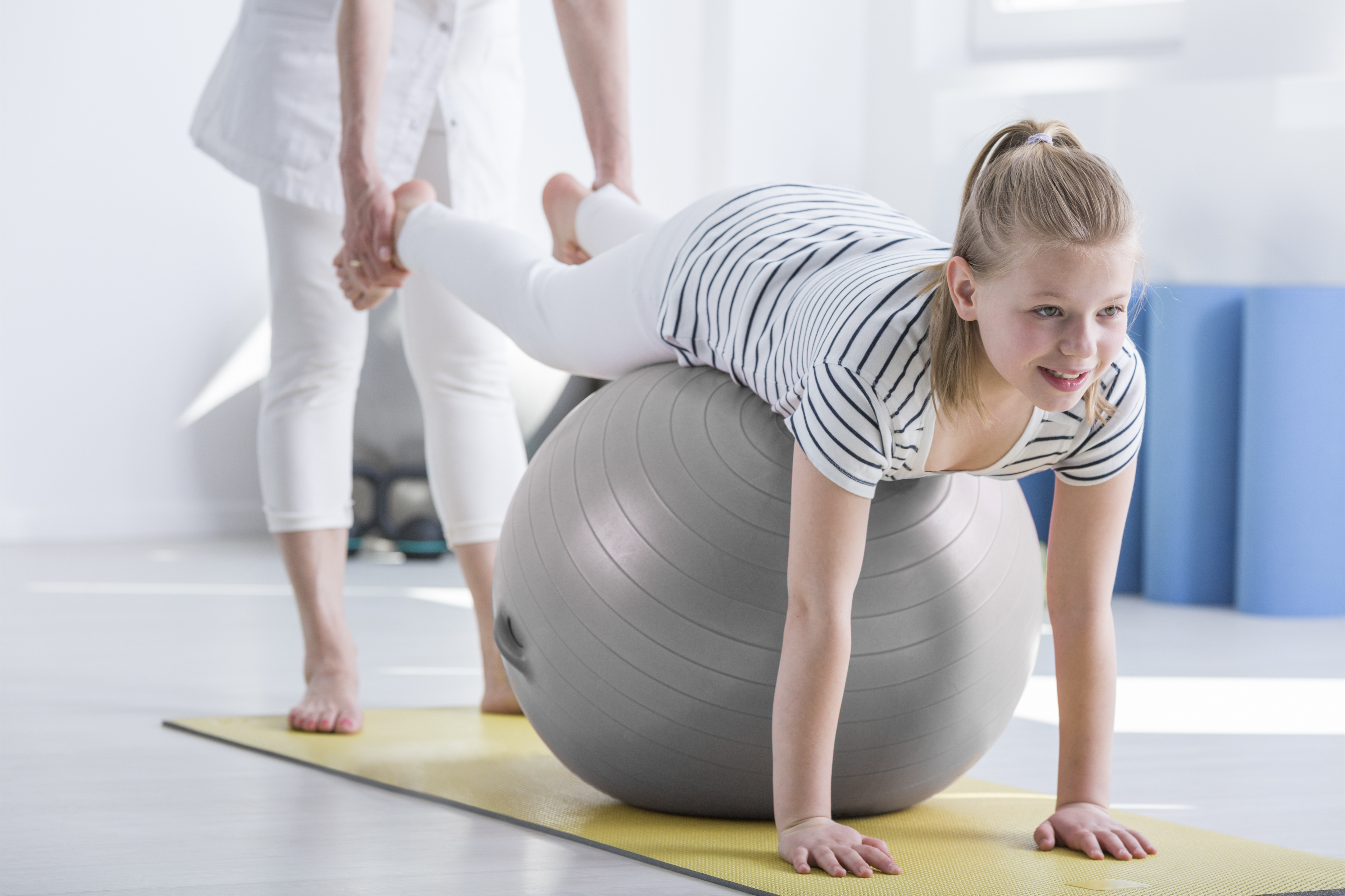 Smiling young girl lying on ball during pediatric occupational therapy